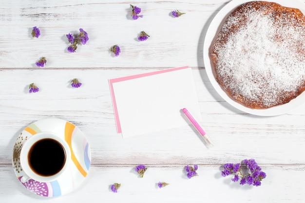 Filiżanka Kawy, Domowe Ciasto, Kartka Papieru I Wiele Małych Fioletowych Kwiatów Premium Zdjęcia