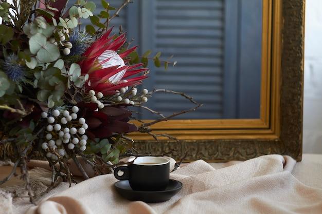 Filiżanka Kawy I Egzotyczny Bukiet Stoi Na Stole Z Beżowym Lnianym Obrusem Na Starej Ramie Premium Zdjęcia