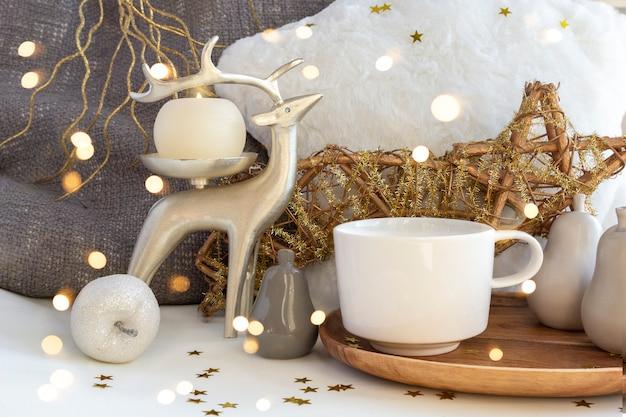 Filiżanka kawy i herbaty na świąteczny skład ze świecami, jeleniami i bombkami świątecznymi Premium Zdjęcia