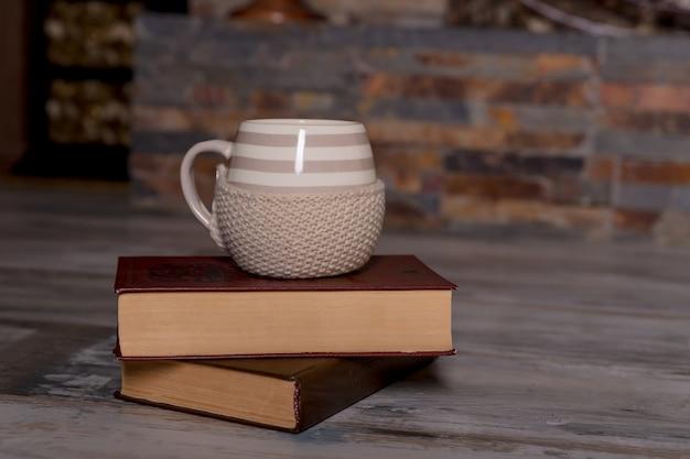 Filiżanka kawy i książka na drewnianym stole w natury tle Premium Zdjęcia
