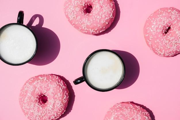 Filiżanka kawy i pączki na różowym tle Darmowe Zdjęcia