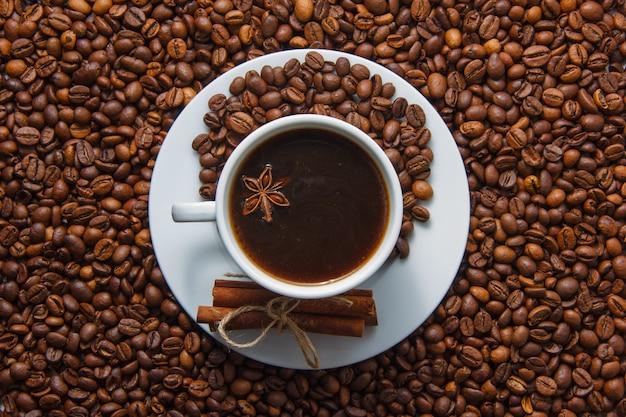 Filiżanka Kawy I Suchy Cynamon Z Kawowymi Fasolami Na Tle. Widok Z Góry. Darmowe Zdjęcia