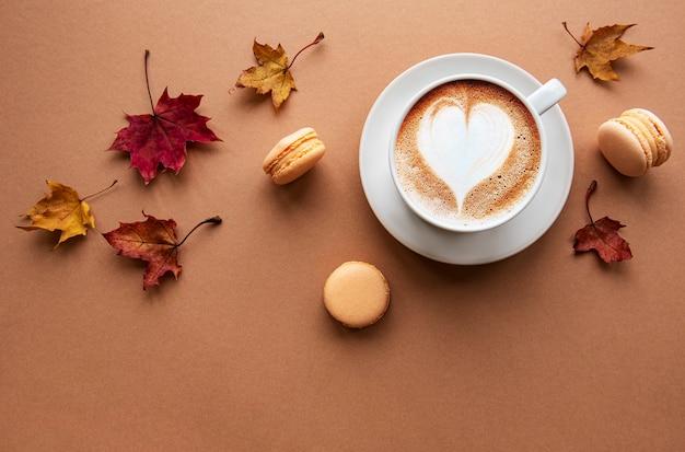 Filiżanka Kawy I Suchych Liści Na Brązowym Tle. Leżał Na Płasko, Widok Z Góry, Miejsce Na Kopię Premium Zdjęcia