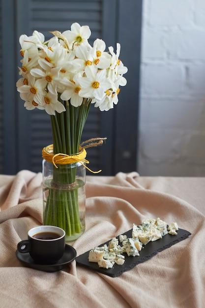 Filiżanka Kawy I Talerz Sera W Pobliżu Dużego Bukietu Białych żonkili Stoi Na Stole Z Beżowym Lnianym Obrusem, Koncepcja świątecznego Poranka Premium Zdjęcia