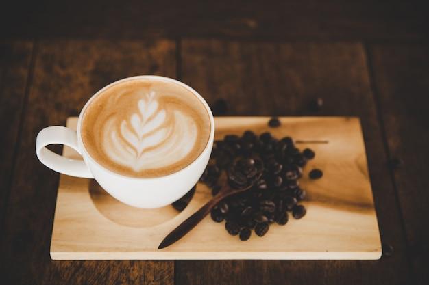 Filiżanka kawy latte na stół z drewna w kawiarni kawiarni Darmowe Zdjęcia