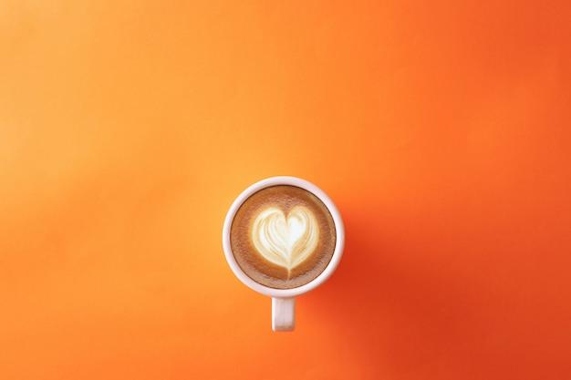 Filiżanka kawy na pomarańczowym tle Premium Zdjęcia
