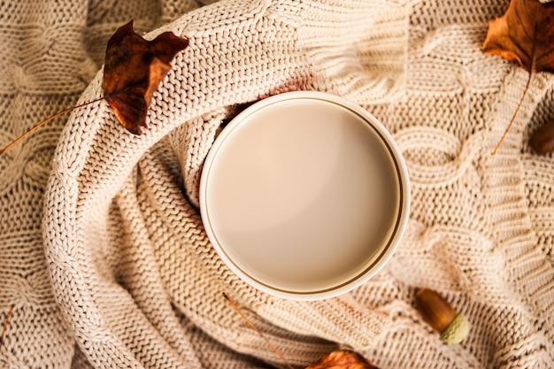 Filiżanka kawy owinięta wełnianym beżowym swetrem Premium Zdjęcia