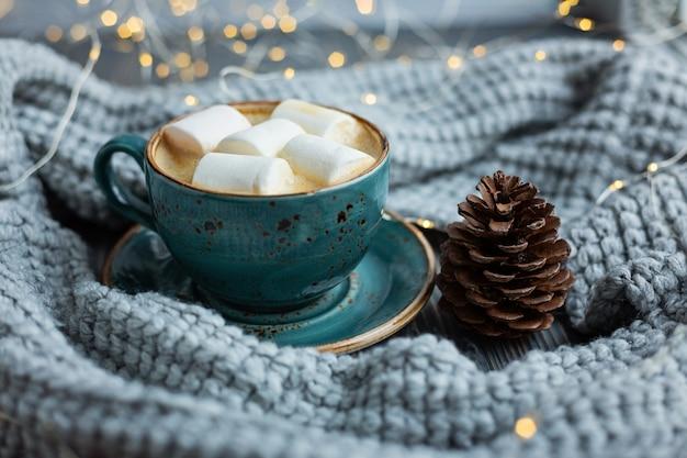 Filiżanka kawy, ptasie mleczko, ciepły sweter z dzianiny. ciepłe światła bokeh Premium Zdjęcia