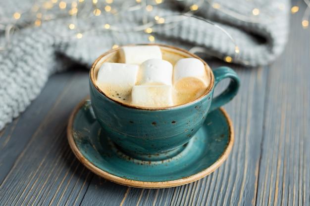 Filiżanka kawy, ptasie mleczko, ciepły sweter z dzianiny na drewnie Premium Zdjęcia