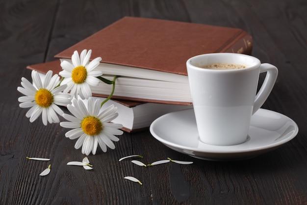 Filiżanka Kawy, Rumianek I Książka Na Drewnianym Stole Premium Zdjęcia