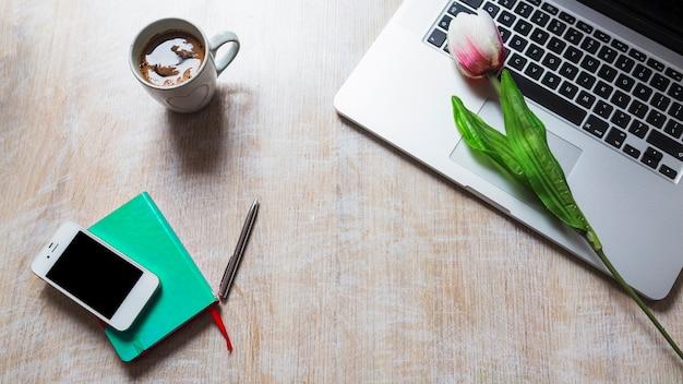 Filiżanka kawy; tulipan na laptopie; komórka; pióro i książka na drewnianym stole Darmowe Zdjęcia