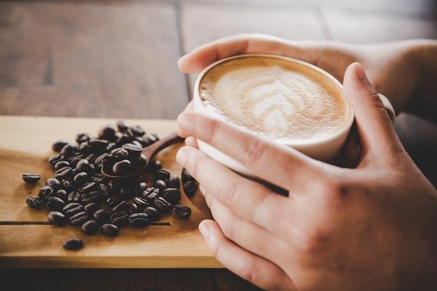 Filiżanka kawy w ręce kobiet na tekstury drewna. Darmowe Zdjęcia
