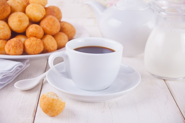 Filiżanka kawy z małymi piłkami świeżo piec domowej roboty serowy pączek w talerzu na tle. Premium Zdjęcia