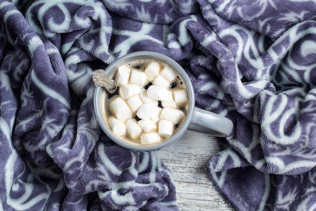 Filiżanka kawy z piankami i ciepłą kratę na białym drewnianym stole. koncepcja bożego narodzenia zima. Premium Zdjęcia
