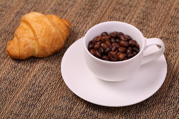 Filiżanka kawy z rogalikiem i świeżymi ziarnami kawy Premium Zdjęcia