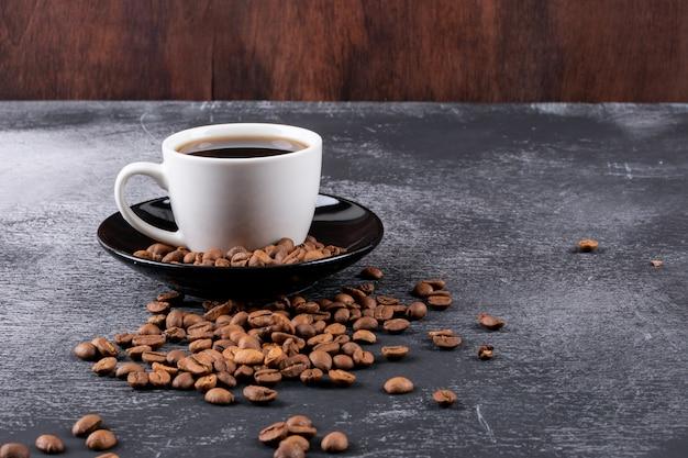 Filiżanka Kawy Z Ziaren Kawy Na Ciemnym Stole Darmowe Zdjęcia