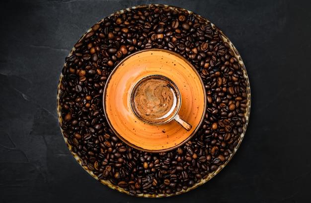Filiżanka Z Kawą Espresso Ułożona Na Ciemnym Stole. Wokół Filiżanki Kawy Znajdują Się Palone Ziarna Kawy. Widok Z Góry Premium Zdjęcia