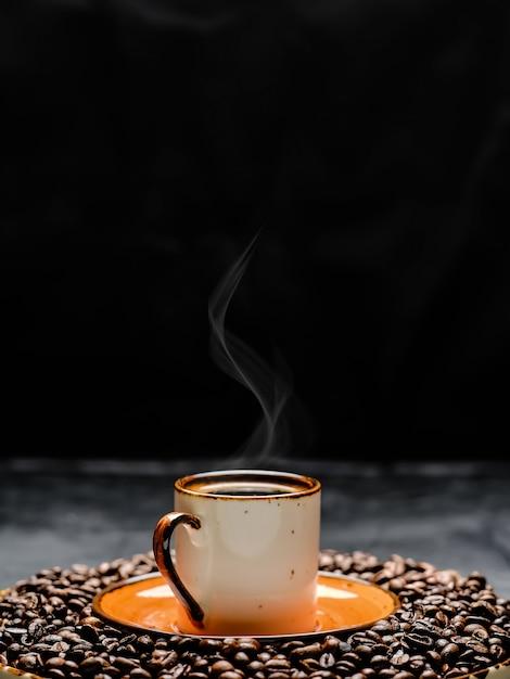 Filiżanka Z Kawą Espresso Ułożona Na Ciemnym Stole. Wokół Filiżanki Kawy Znajdują Się Ziarna Palonej Kawy, Z Bliska, Selektywne Skupienie Premium Zdjęcia