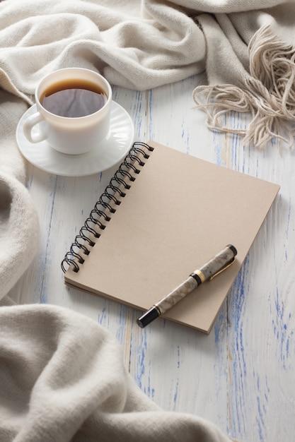 Filiżanka Z Kawą, Notatnik Na Białym Drewnianym Stole. Pojęcie Wiosny Premium Zdjęcia