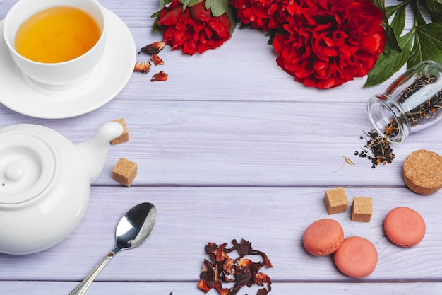 Filiżanka zielona herbata na stole z świeżymi peonia kwiatami Premium Zdjęcia