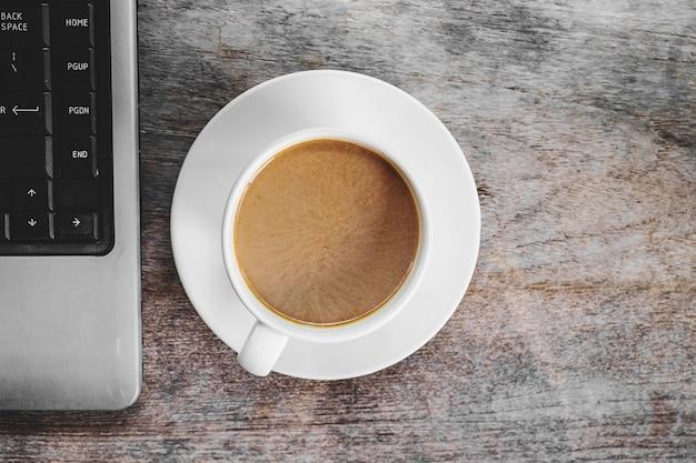 Filiżanki do kawy i laptopy na biurku Premium Zdjęcia