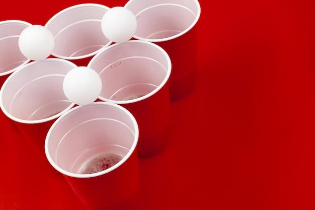 Filiżanki i plastikowa piłka na czerwonym tle. gra pong piwny Premium Zdjęcia