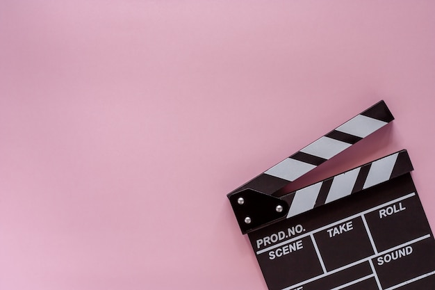 Film deska klapy na różowym tle do filmowania sprzętu Premium Zdjęcia