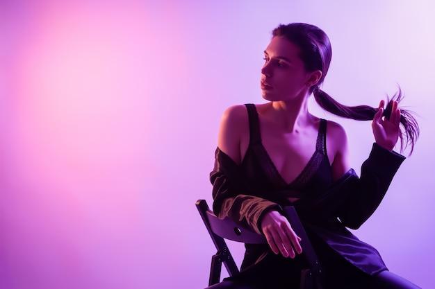 Filmowa Noc Portret Kobiety W Neonie. Piękna Młoda Kobieta W Stylowe Ubrania Pozowanie Na Krześle W Kolorowe światła. Premium Zdjęcia