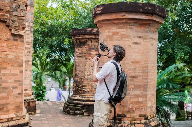 Filmowiec-mężczyzna Kręci Wideo W Elektronicznym Stabilizatorze, Steadycam Aby Kręcić W Po Nagar Cham Tovers. Koncepcja Technologii Cyfrowej. . Premium Zdjęcia