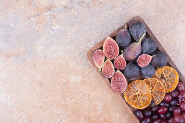 Fioletowe Figi Z Suchymi Plastrami Pomarańczy I Jagodami Dereń Na Drewnianej Desce Darmowe Zdjęcia