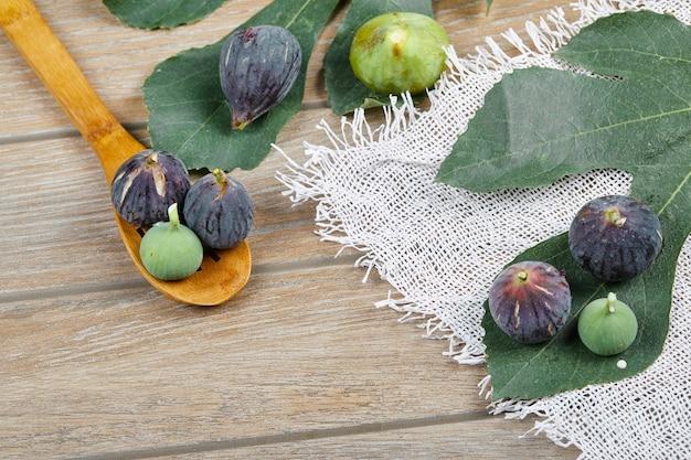 Fioletowo-zielone Figi Na Drewnianym Stole Z Białym Obrusem I Liściem, Drewniana łyżka. Darmowe Zdjęcia
