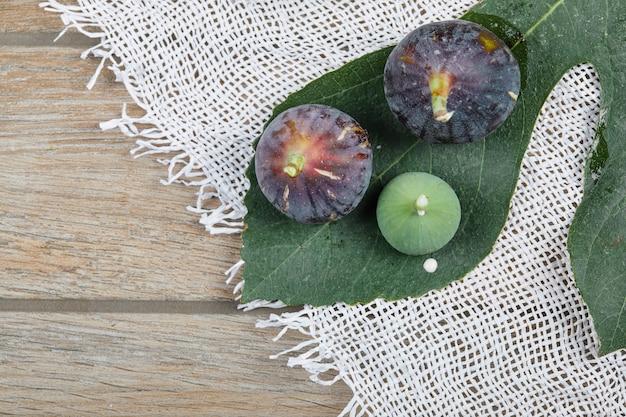 Fioletowo-zielone Figi Na Drewnianym Stole Z Białym Obrusem I Liściem. Darmowe Zdjęcia