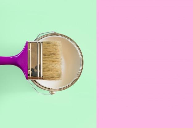Fioletowy pędzel z otwartą puszką białej farby na neo miętowym i różowym tle. koncepcja trendu. Premium Zdjęcia