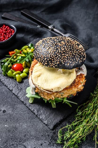 Fishburger Z Czarną Bułką Brioche, Omletem, Kotletem Rybnym I Rukolą. Widok Z Góry Premium Zdjęcia