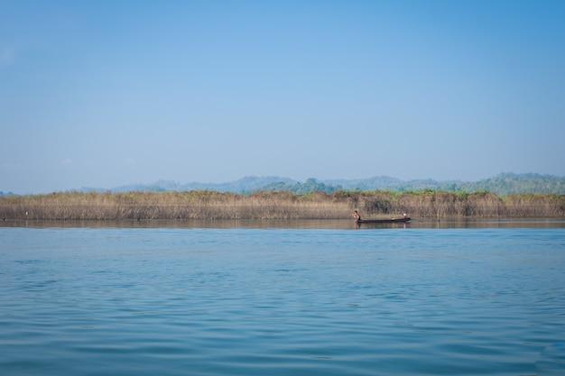 Fisher mężczyzna na łodzi na pięknej rzece i górze Premium Zdjęcia