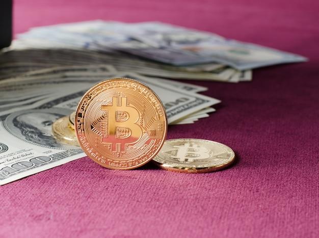 Fizyczna Złocista Bitcoin Moneta Przeciw Dolarowym Rachunkom Na Purpurowym Tle. Premium Zdjęcia