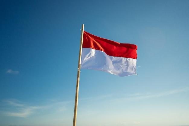 Flaga Indonezji Pod Błękitnym Niebem Podnosząca Biało-czerwoną Flagę Premium Zdjęcia