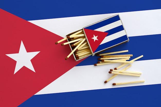Flaga Kuby Jest Pokazana Na Otwartym Pudełku Zapałek, Z Którego Wypada Kilka Zapałek I Leży Na Dużej Fladze Premium Zdjęcia