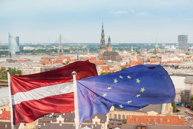Flagi łotwy I Europy Z Riga Cityscape Na Tle Premium Zdjęcia