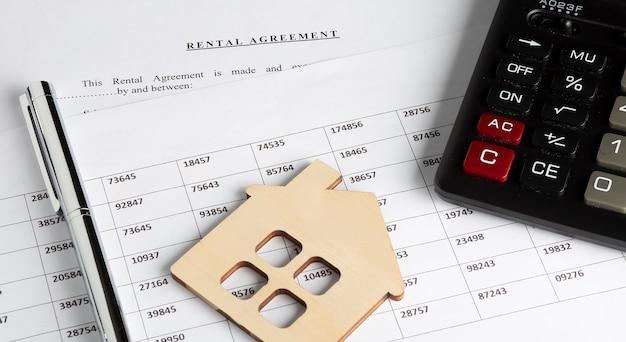 Formularz Umowy Najmu Na Pulpicie Z Długopisem, Modelem Drewnianego Domu, Wykresem I Kalkulatorem Premium Zdjęcia