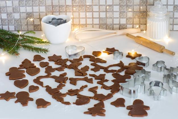 Formy do pieczenia, rozwałkowane ciasto na pierniczki, mąkę, girlandę i wałek do ciasta Premium Zdjęcia
