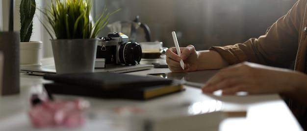 Fotograf Kobieta Pracuje Z Makietą Tabletu Na Stole Z Aparatem I Dostawami W Studio Premium Zdjęcia