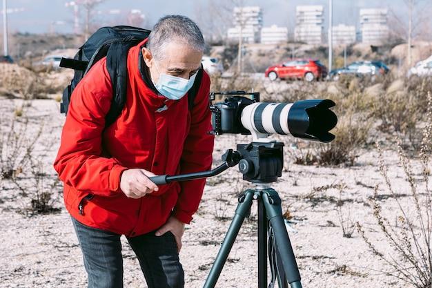 Fotograf W Masce Chirurgicznej Wykonujący Zdjęcia I Wideo Na Ulicy Przy Użyciu Statywu Premium Zdjęcia