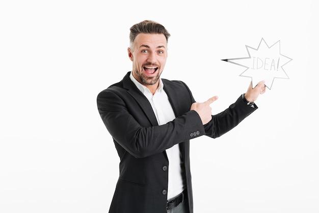 Fotografia Z Podnieceniem Szczęśliwy Biznesmen Jest Ubranym Formalne Ubrania Wskazuje Na Mowie Gulgocze Z Słowo Pomysłem Trzyma W Ręce, Odizolowywająca Nad Biel ścianą Premium Zdjęcia