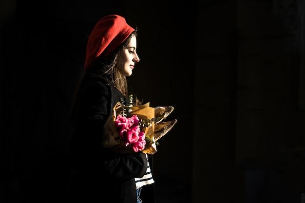 Francuska kobieta z bagietkami na ulicie w berecie Darmowe Zdjęcia