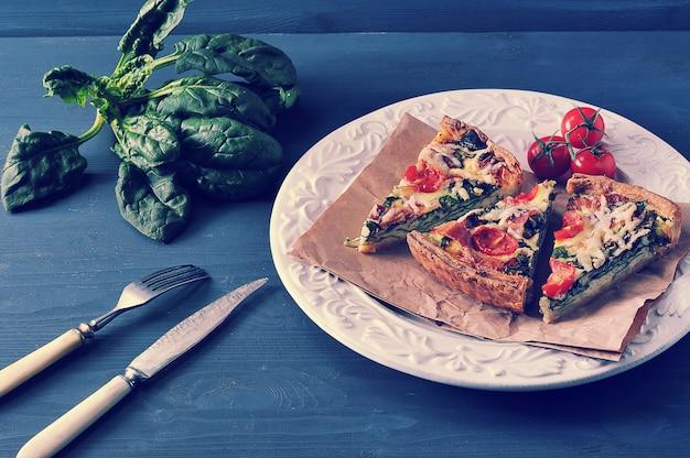 Francuski Quiche Z Jajkami, świeżym Szpinakiem, Pomidorami I Boczkiem Premium Zdjęcia