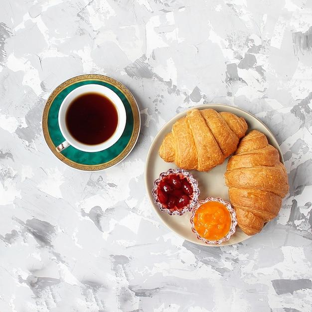 Francuskie śniadanie z rogalikami, dżemem morelowym, dżemem wiśniowym i filiżanką herbaty, czerwonymi i żółtymi kwiatami Darmowe Zdjęcia