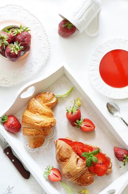 Francuskie śniadanie z rogalikiem i dżemem truskawkowym Premium Zdjęcia