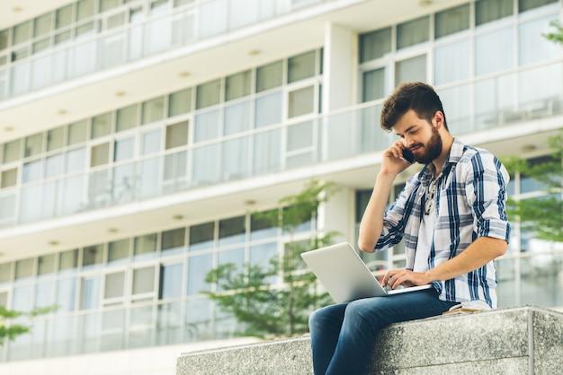 Freelancer używa laptop i telefon outdoors na letnim dniu Darmowe Zdjęcia