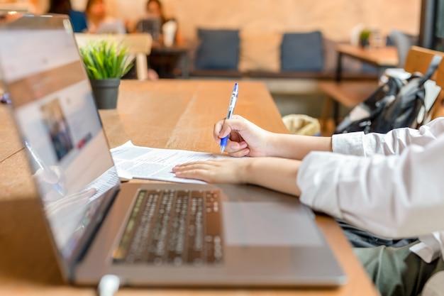 Freelancer wypełnia dokument formularz z laptopem otwartym na drewnianym stole. Premium Zdjęcia
